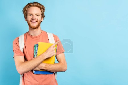 redhead student holding notebooks and pointing with finger on blue