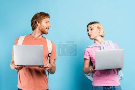 Photo pour Curieux jeunes étudiants regardant les uns les autres ordinateurs portables sur bleu - image libre de droit