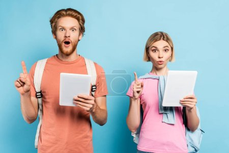 Photo for Surprised young students holding digital tablets and showing idea sign on blue - Royalty Free Image