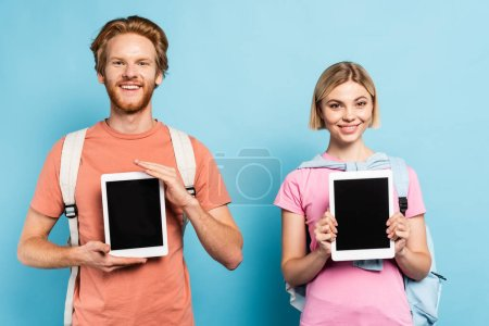 Photo for Blonde and redhead students holding digital tablets with blank screen on blue - Royalty Free Image