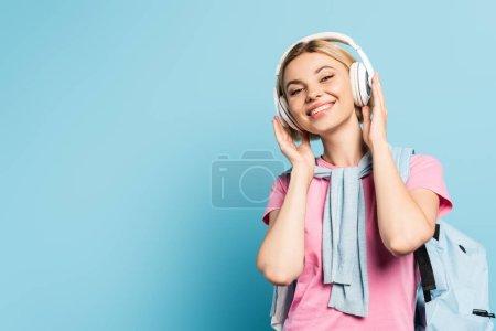 blonde student listening music in wireless headphones on blue