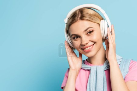 Photo pour Femme blonde écouter de la musique dans les écouteurs sans fil sur bleu - image libre de droit