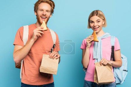 Photo pour Jeunes étudiants tenant des sacs en papier et mangeant du pain grillé sur bleu - image libre de droit