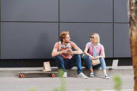Photo pour Foyer sélectif des étudiants dans des lunettes assis près du skateboard et des gadgets tout en se regardant à l'extérieur - image libre de droit