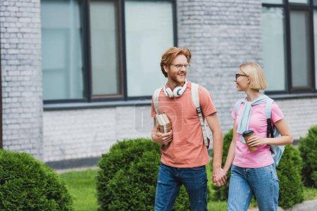 junge Studenten in Brillen, die sich an den Händen halten und einander beim Gehen in der Nähe des Campus anschauen