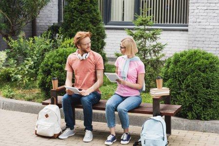 Photo pour Étudiants barbus et blonds assis sur le banc près des livres, des tasses en papier et des sacs à dos tout en tenant des tablettes numériques - image libre de droit