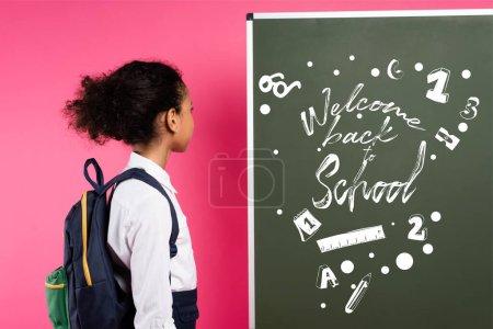 Foto de Colegiala afroamericana mirando pizarra con bienvenida de nuevo a la escuela letras en rosa - Imagen libre de derechos