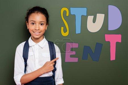 Photo pour Afro-américaine écolière pointant avec le doigt au tableau vert avec lettrage étudiant - image libre de droit