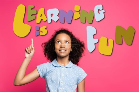 curly african american kid pointing with finger and looking up near learning is fun lettering on pink