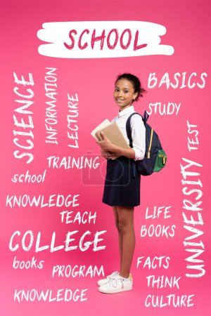 Photo for African american schoolgirl with backpack holding books near school lettering on pink - Royalty Free Image