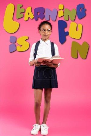 Photo pour Afro-américaine écolière en lunettes lecture livre près de l'apprentissage est lettrage amusant sur rose - image libre de droit