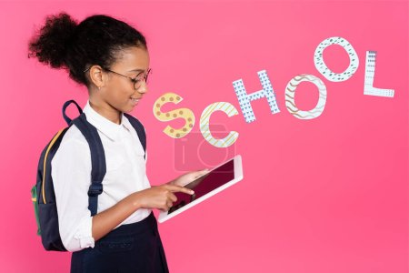 Photo for African american schoolgirl in glasses with backpack using digital tablet near school lettering on pink - Royalty Free Image