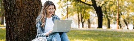 Photo pour Concept panoramique de femme utilisant un ordinateur portable tout en étant assis sous le tronc d'arbre - image libre de droit