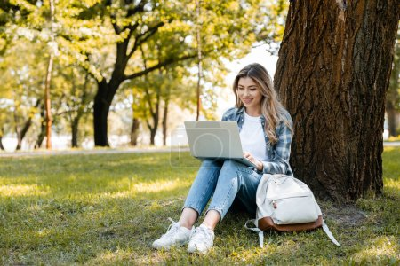 Photo for Woman using laptop while sitting under tree trunk on grass - Royalty Free Image