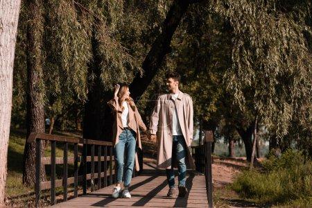 Photo pour Femme touchant chapeau de paille et regardant petit ami tout en marchant sur le pont en bois - image libre de droit