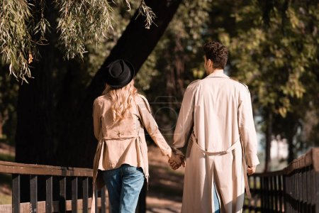 back view of couple in trench coats holding hands and walking on wooden bridge in autumnal park