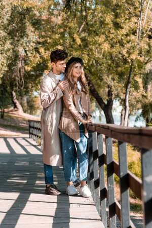 man touching shoulders of woman in hat and trench coat standing on wooden bridge in autumnal park