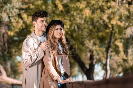 Photo for Selective focus of man touching shoulders of woman in hat and trench coat in autumnal park - Royalty Free Image