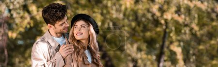 panoramic crop of man touching shoulders of woman in hat and looking at each other in autumnal park