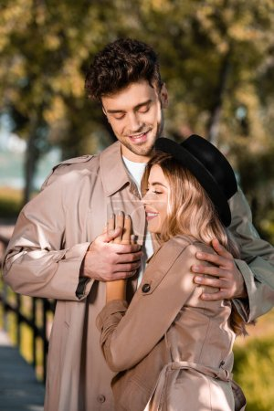 man in trench coat hugging and touching hand of woman in hat outside