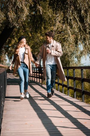 excited couple in trench coats holding hands and walking on wooden bridge