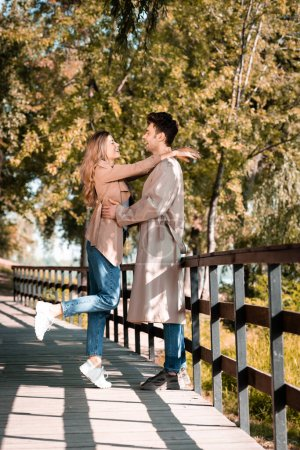 Photo for Side view of excited couple hugging while standing on wooden bridge - Royalty Free Image
