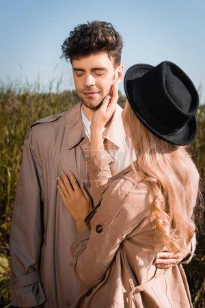 Photo pour Femme blonde au chapeau touchant le visage de l'homme en trench coat à l'extérieur - image libre de droit