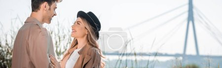 panoramic shot of woman in hat and man looking at each other outside