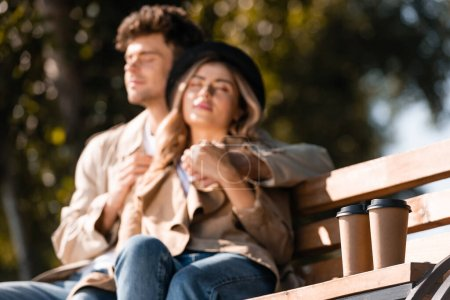 Photo for Selective focus of paper cups near blonde woman in hat and man in trench coat sitting on bench - Royalty Free Image