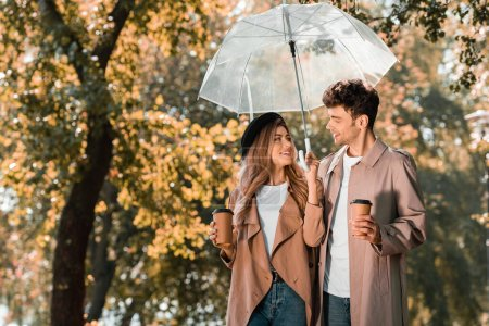 Photo for Couple in trench coats standing under umbrella and holding paper cups with coffee to go - Royalty Free Image