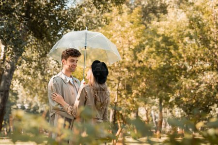 selective focus of woman in hat and man in trench coat standing under umbrella in autumnal park