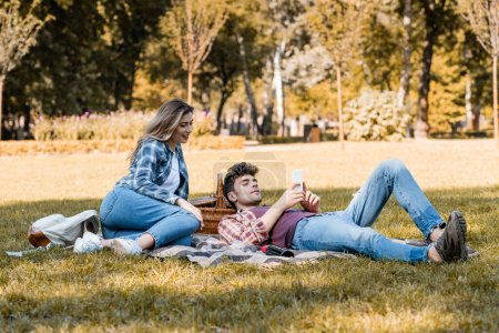Photo for Woman and man looking at smartphone while resting on blanket in park - Royalty Free Image