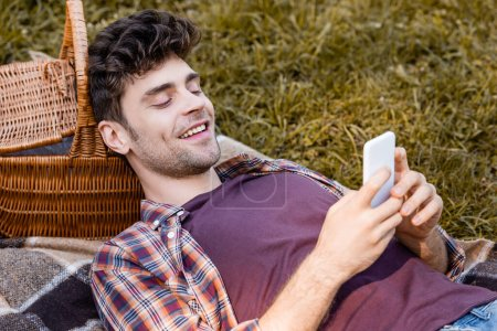 man looking at smartphone while lying on blanket near wicker basket