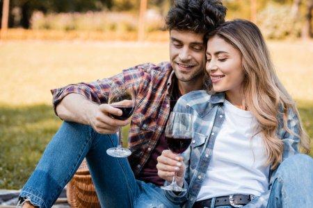 Photo pour Homme et femme tenant des verres avec du vin rouge pendant le pique-nique - image libre de droit
