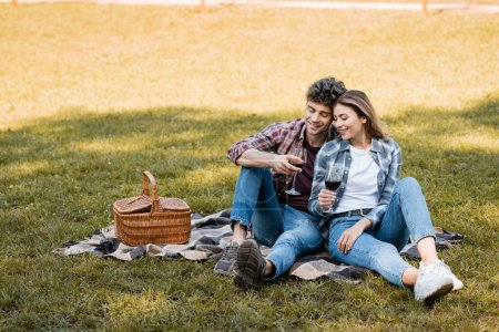 couple sitting on plaid blanket and holding glasses of red wine