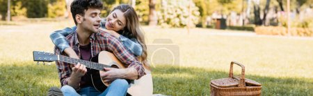 panoramic shot of woman sitting on plaid blanket and touching boyfriend playing acoustic guitar