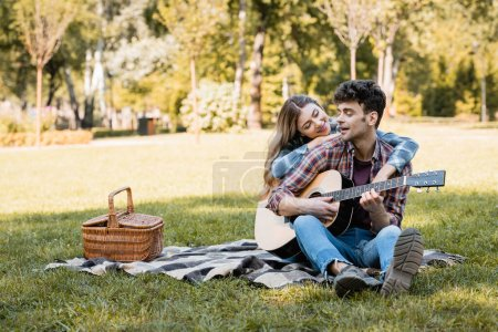 woman sitting on plaid blanket near wicker basket and touching boyfriend playing acoustic guitar