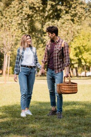 Photo pour Homme avec panier en osier tenant la main avec sa petite amie tout en marchant dans le parc - image libre de droit
