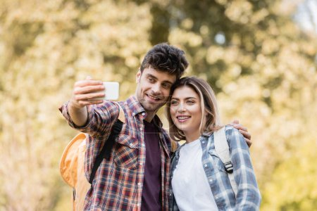 Photo for Joyful man and woman taking selfie in autumnal park - Royalty Free Image