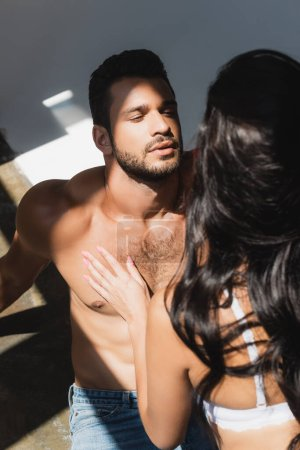 Photo for Selective focus of brunette woman touching shirtless man on grey - Royalty Free Image