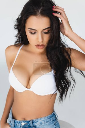 Photo for Sexy young woman in bra touching hair and looking down isolated on grey - Royalty Free Image