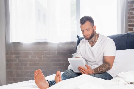 tattooed man in white t-shirt sitting in bed near window and using digital tablet