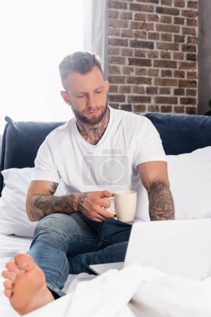 Photo for Selective focus of tattooed teleworker sitting in bed with cup of tea and using laptop - Royalty Free Image