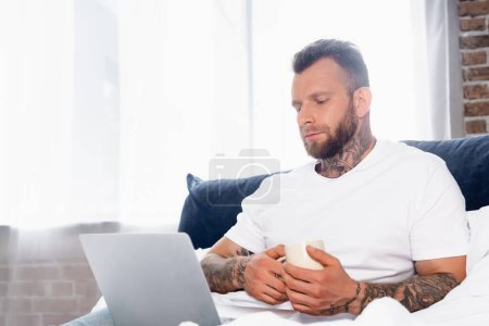 Photo for Young tattooed freelancer using laptop while sitting in bedroom with cup of tea - Royalty Free Image
