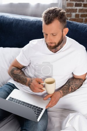Photo for Tattooed freelancer using laptop while sitting in bed with cup of tea - Royalty Free Image