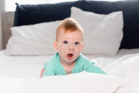 Foto de Enfoque selectivo del niño mirando a la cámara con la boca abierta mientras se arrastra en la cama - Imagen libre de derechos
