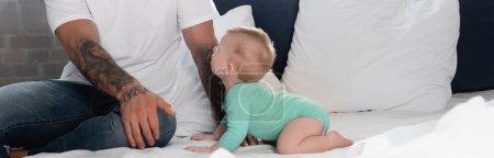 Säugling im Babystrampler krabbelt auf Bett neben Vater