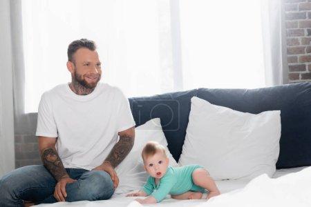 podekscytowany młody człowiek w białej koszulce i dżinsach siedzi obok chłopca czołgającego się na łóżku z otwartymi ustami