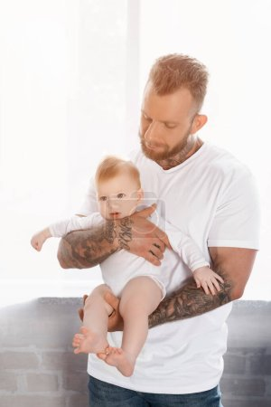 young bearded man in white t-shirt holding infant child in baby romper