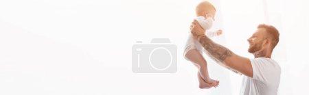 Photo pour Vue latérale du jeune homme tatoué tenant son fils en bas âge dans les mains tendues, en-tête du site - image libre de droit